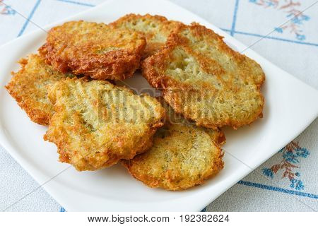 Fried pancakes with potato on white plate