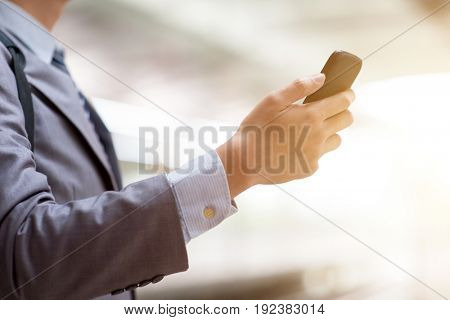 Business people hand using smart phone outdoors, bright sun flare background.