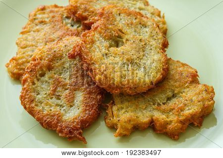 Fried pancakes with potato on green plate
