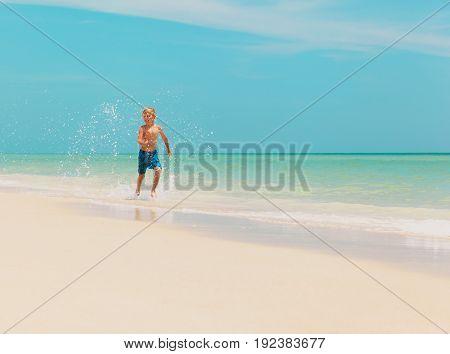 little boy run play with waves on tropical beach