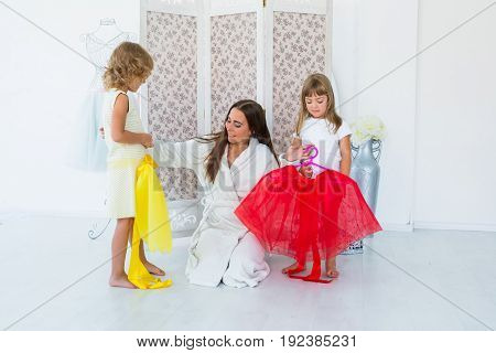 Woman with children trying on dress in the bedroom