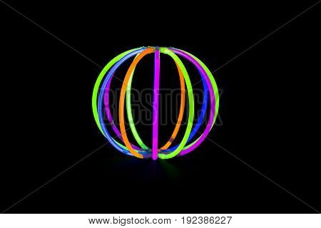 Ball made with glow sticks neon light fluorescent on back background. variation of different colored chem lights like a ball