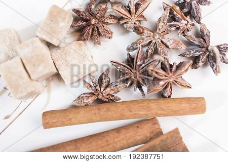 Cinnamon sticks anise stars and pieces of brown sugar lie on white background close-up