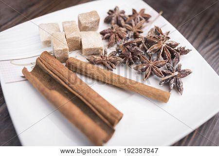 Cinnamon sticks anise stars and pieces of brown sugar lie on a white square saucer on a brown wooden background