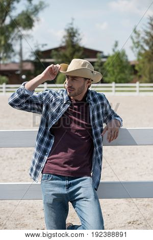 handsome man wearing cowboy hat and checkered shirt leaning on fence at ranch