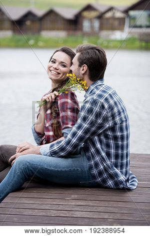 happy couple embracing on pier while girl holding yellow flowers