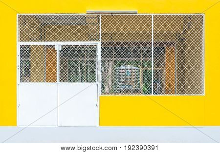 Closeup To Metal Entrance Door Of Concrete Yellow Factory Warehouse