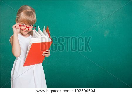 Red holding girl book elementary age green background