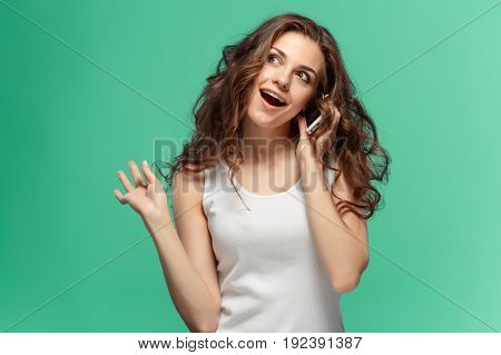 The young woman's portrait with happy emotions and mobile phone at studio