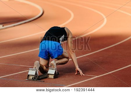 male runner starting blocks of 400-meter sprint at competition
