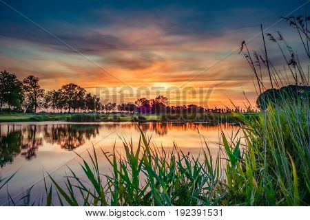 A Dutch polder landscape with a water pool along an old sea dike. The sun gives a splendid atmosphere to the tranquility of the podler landscape and transforms it into a classic romantic picture