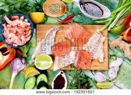 Arrangement of Raw Ingredients of Thai Fish Cakes with Fillet of Salmon and Cod Prawns and Vegetables Spices and Sauces closeup on Cracked Wooden background. Top View