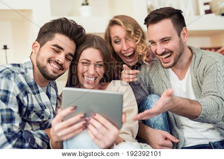 Happy young people enjoying time togetherusing tablet.