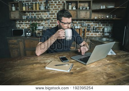 concentrated bearded man drinking coffee and working with laptop in home office