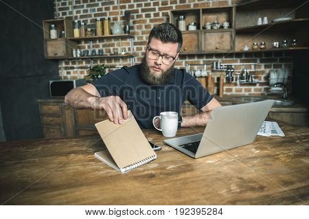 concentrated bearded freelancer looking at notepad while sitting at table with laptop in the kitchen
