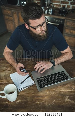 High angle view of bearded young man using smartphone and laptop during work at home