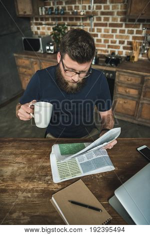 high angle view of man with coffee cup in hand reading newspaper at kitchen