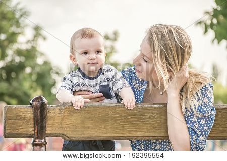 Beautiful happy mather with baby boy outdoor on nature at sunny summer say