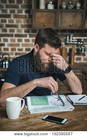 portrait of tired man rubbing eyes while reading newspaper at home