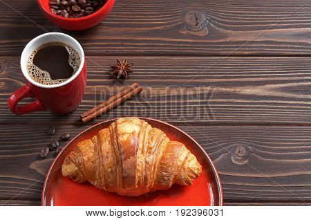 Cup of hot coffee and croissant on dark wooden background. Space for text. Red tableware
