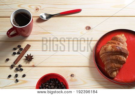 Cup of hot coffee and fresh croissant for breakfast on wooden table. Red tableware