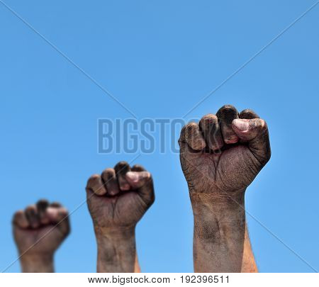 Three dirty male fists raised up on a blue background