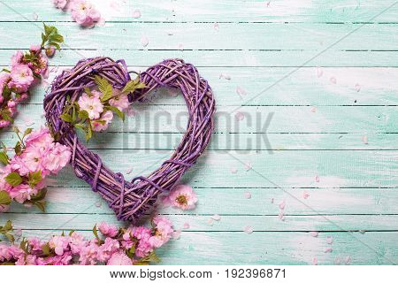 Big decorative heart and pink flowers on turquoise wooden background. Selective focus. Top view. Place for text.