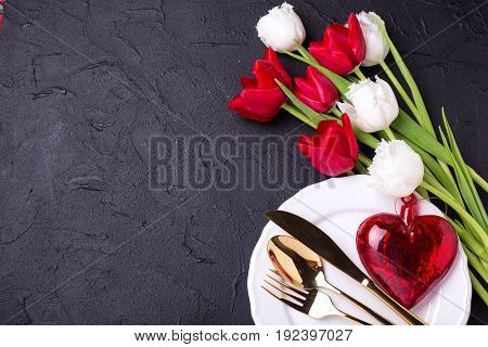 Festive table setting. White plate golden cutlery decorative red heart and white and red tulips flowers on black textured backgroud. Selective focus. Top view. Place for text.
