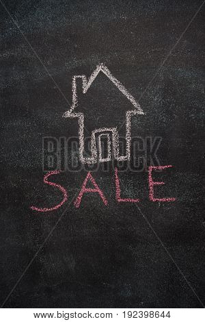 House with sale word drawn with chalk on blackboard