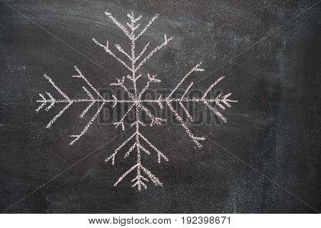 Big snowflake drawn with white chalk on blackboard