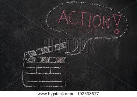 Open movie clapper and speech bubble with action word drawn with chalk on blackboard