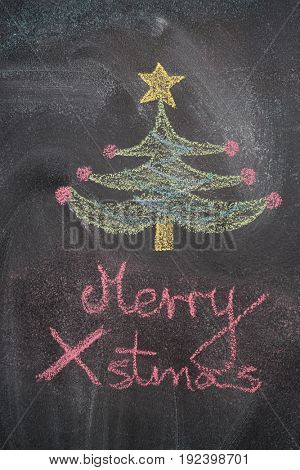 Christmas tree with Merry Xmas writing drawn with white chalk on blackboard