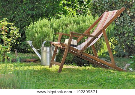 deck chair on a rural garden with watering can