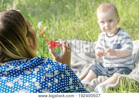 Young mather inflating soap bubbles for baby boy sitting on grass