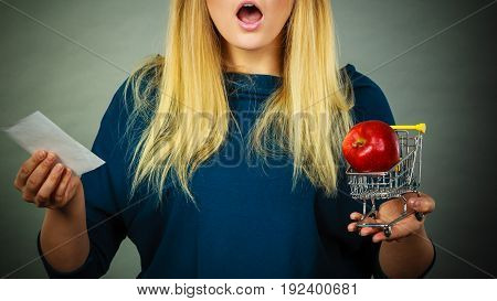 Shocked woman holding shopping basket with fruits looking at bill receipt being scared of huge prices