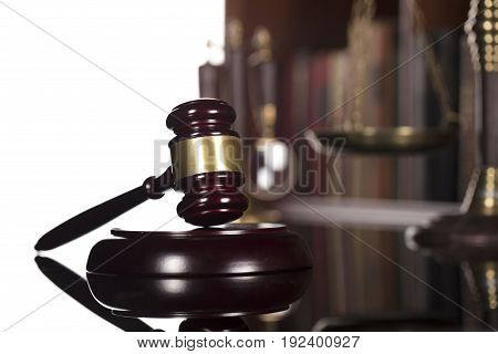 Gavel of the jugde, scale of justice andThemis in the court library.