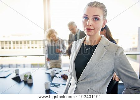 Portrait of a focused young businesswoman standing in a modern office with a group of colleagues working in the background