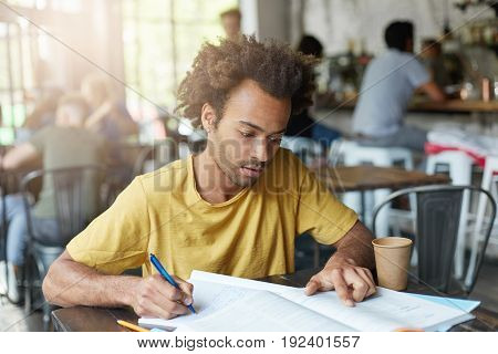 Casually Dressed Young Black Male Student With Beard And Curly Hair Having Focused Concentrated Look