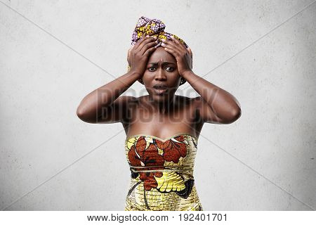 Sorrorful African Dark-skinned Middle-aged Woman In Traditional Clothes Holding Her Hands On Head Lo