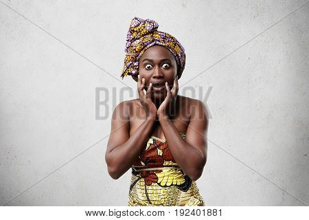 Portrait Of Funny Emotional Astonished Black Woman In Bright Clothing Keeping Hands On Her Face, Ast