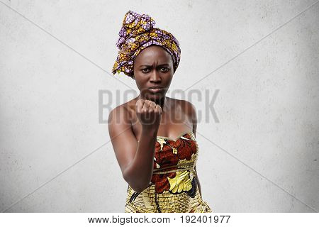 Menacing Black Woman With Big Eyes And Full Lips Wearing Colorful Scarf On Head And Dress Showing He