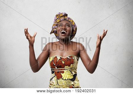 Energetic Glad Woman With Dark Skin Wearing Scarf On Head And Fashionable Dress Looking Up Raising H