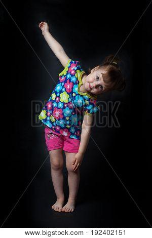 Little girl doing gymnastics. isolated, black background