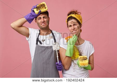 Tired And Untidy Couple After Doing Housework. Young Man Wearing Apron Holding Mop, Brush And Beauti