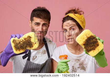 Male And Female In Casual Clothes Having Dirty Faces Demonstrating Dirty Sponges After Cleaning Hous