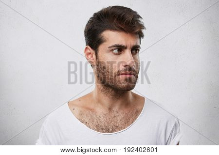 Sideways Portrait Of Strong Male With Beard And Stylish Hairstyle Wearing White T-shirt Looking Asid