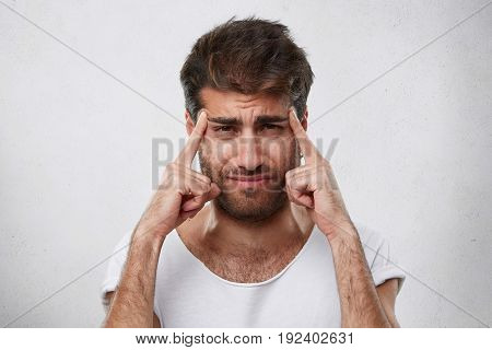 Young Macho Man With Thick Beard And Trendy Hairstyle Holding His Fingers On Temples Trying To Conce