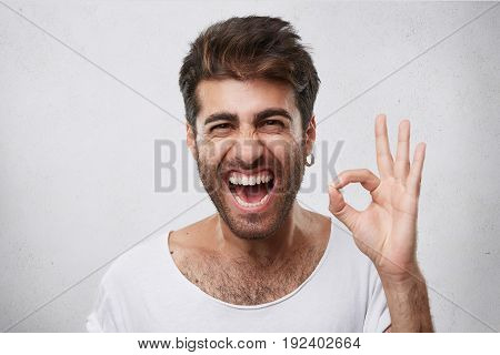 Attractive Man With Beard Closing His Eyes And Opening Mouth With Joy Showing Ok Sign Being Glad Aft