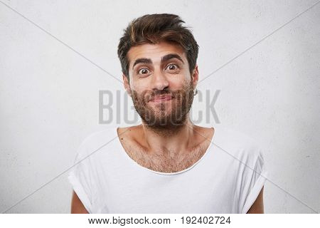 Excited Man With Thick Dark Eyebrows And Beard Being Pleasantly Surprised Looking With Wide Opened E