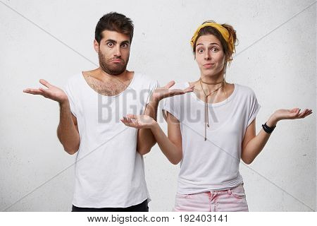 Clueless And Puzzled Stylish Male And Female Standing At White Wall With Copy Space For Your Text, H